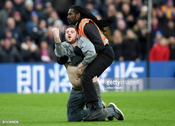 A fan runs onto the pitch and is challenged by a steward during the Premier League match between Crystal Palace and Newcastle United at Selhurst Park...