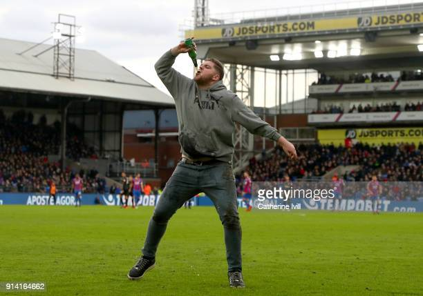 A fan runs onto the pitch during the Premier League match between Crystal Palace and Newcastle United at Selhurst Park on February 4 2018 in London...