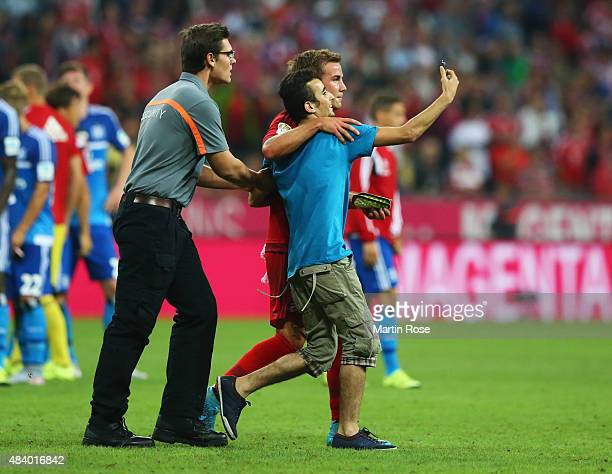 A fan runs onto the pitch to take a 'selfie' photograph with Mario Goetze of Bayern Munich after the Bundesliga match between FC Bayern Muenchen and...