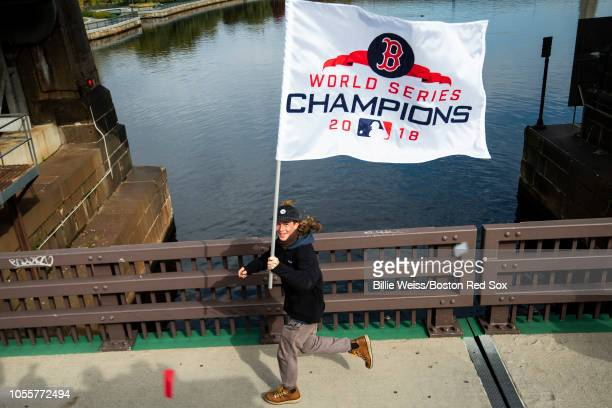 A fan runs with a flag during the of the Boston Red Sox 2018 World Series rolling rally parade on October 31 2018 in Boston Massachusetts