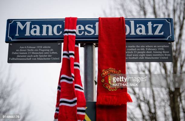 Fan scarves are seen on a 'Manchesterplatz' street sign during a ceremony to commemorate the victims of a plane crash in icy weather 60 years ago in...