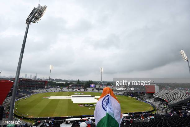 Fan shelters from the rain as play is delayed during the Semi-Final match of the ICC Cricket World Cup 2019 between India and New Zealand at Old...