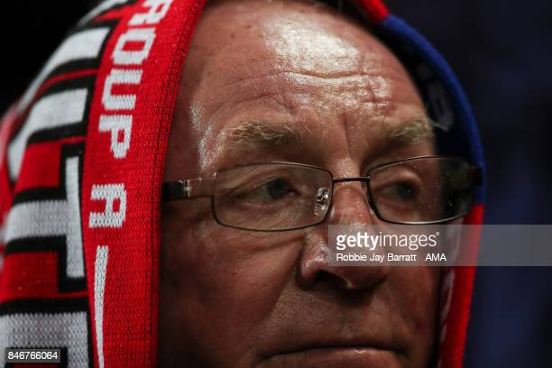 A fan shields from the rain under a scarf during the UEFA Champions League match between Manchester United and FC Basel at Old Trafford on September...