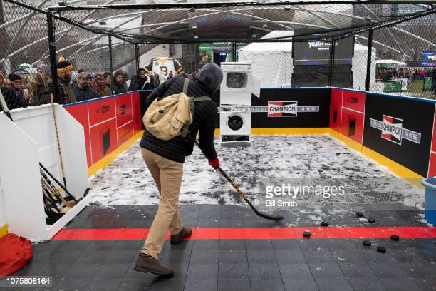 A fan shoots pucks during the Bridgestone NHL Winter Classic Park fan festival at Millenium Park on December 29 2018 in Chicago Illinois