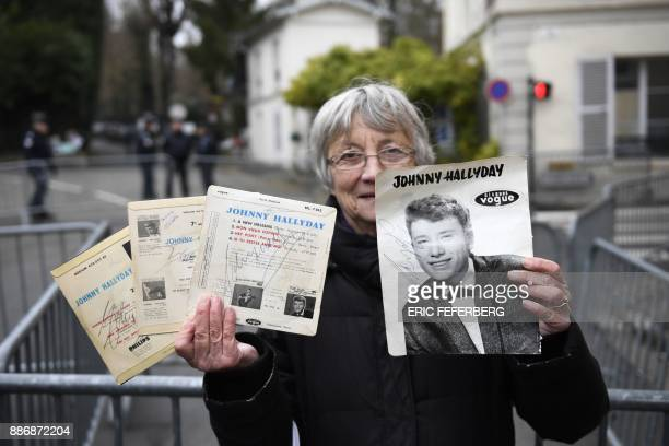 A fan shows her autographs of late French singer and actor Johnny Hallyday as she stands near his house in MarneslaCoquette on December 6 2017...