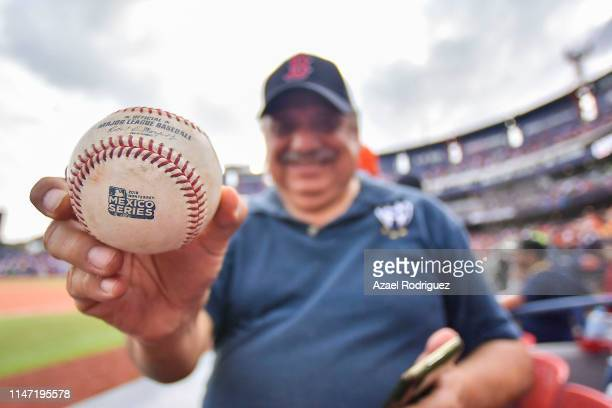 Fan shows the ball he catched during the Houston Astros vs Los Angeles Angels of Anaheim match as part of the Mexico Series at Estadio de Beisbol...