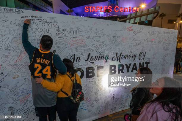 A fan signs a memorial wall near Staples Center in remembrance of former NBA great Kobe Bryant who along with his 13yearold daughter Gianna died...