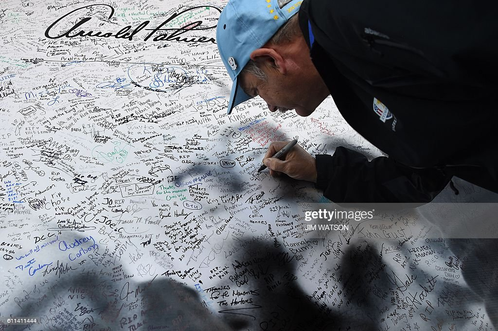 TOPSHOT - A fan signs a tribute wall for American golfer Arnold Palmer at Hazeltine National Golf Course ahead of the 41st Ryder Cup at Hazeltine National Golf Course in Chaska, Minnesota, September 29, 2016. / AFP / JIM