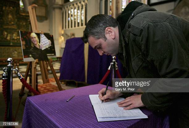 A fan signs snooker player Paul Hunter's memorial book beside his coffin at Leeds Parish Church on October 17 2006 in Leeds England The threetime...