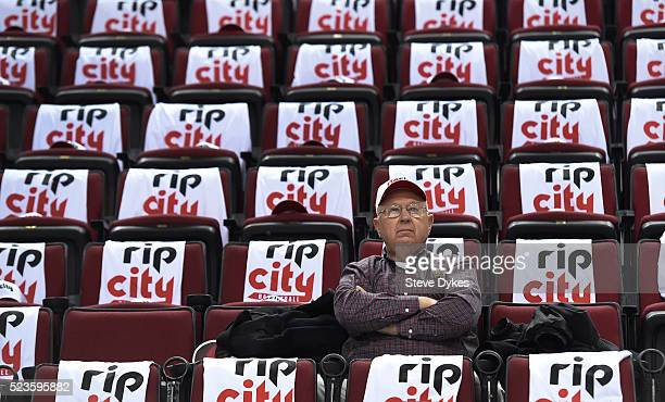 Fan sits in his seat surrounded by free t-shirts and hats laid out on the seats before Game Three of the Western Conference Quarterfinals during the...