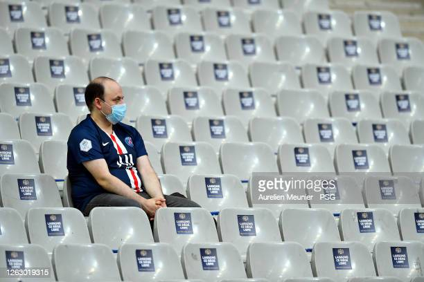 Fan sits in the middle of empty seats due to the Coronavirus pandemic social distancing during the French League Cup final match between Paris...