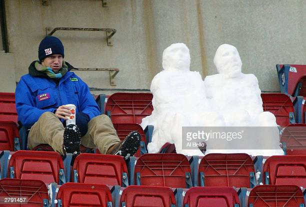 A fan sits next to two snowmen during the game between the New York Giants and the the Washington Redskins on December 7 2003 at Giants Stadium in...