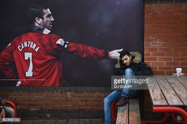 A fan sits on a bench next to a poster showing Manchester United legend Eric Cantona outside Old Trafford stadium before the English Premier League...