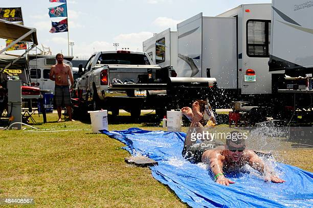 Fan slides on a tarp in the infield before the NASCAR Sprint Cup Series Bojangles' Southern 500 at Darlington Raceway on April 12, 2014 in...
