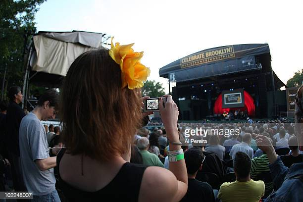 A fan snaps a photograph while she enjoys a performance by a Jazz band called Bitches Brew Revisited that explores Miles Davis' 1970 landmark album...