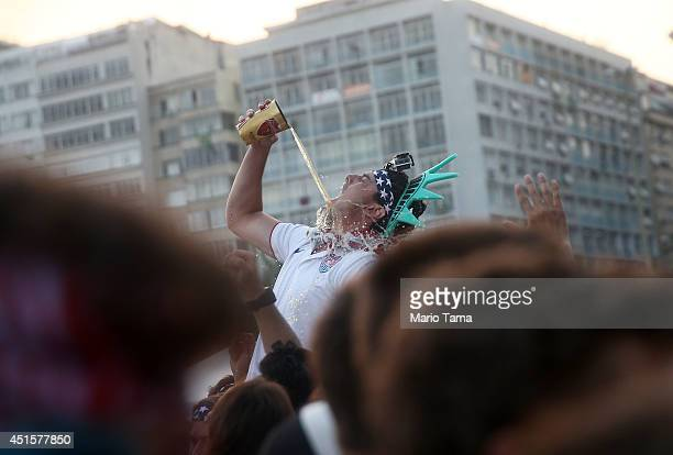 S fan spills while chugging a beer before the start of the US match against Belgium at FIFA Fan Fest on Copacabana Beach on July 1 2014 in Rio de...