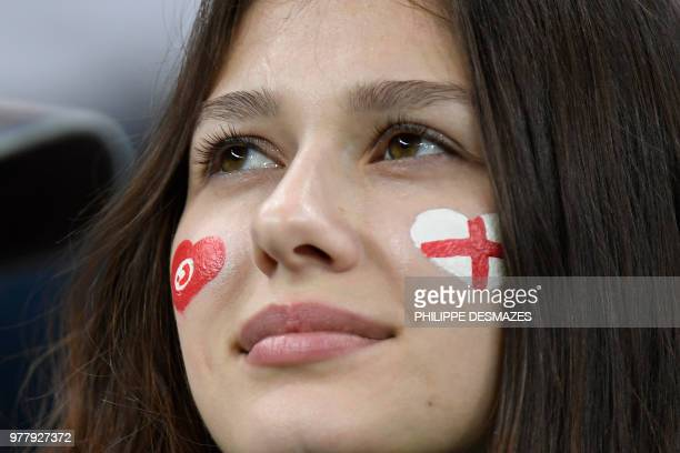A fan sporting Tunisian and English flags painted on her face awaits the start of the Russia 2018 World Cup Group G football match between Tunisia...