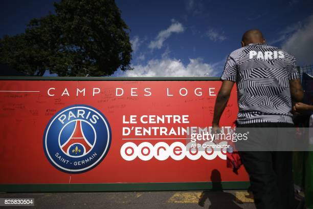 A fan stands in front of the entrance of the Paris SaintGermain's Camp des Loges training centre in SaintGermainenLaye western Paris on August 3 as...