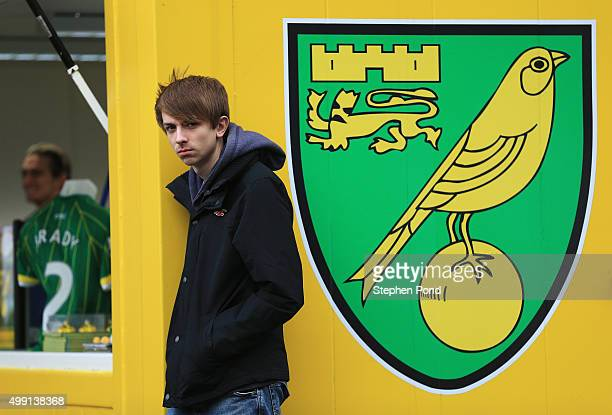 A fan stands next to the Norwich City club crest during the Barclays Premier League match between Norwich City and Arsenal at Carrow Road on November...