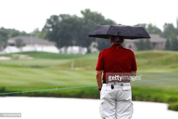 A fan stands with their umbrella as rain starts to fall during the first round of the 3M Championship on August 3 2018 at TPC Twin Cities in Blaine...