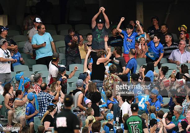 A fan takes a catch in the crowd during the Big Bash League match between the Adelaide Strikers and the Melbourne Stars at Adelaide Oval on December...