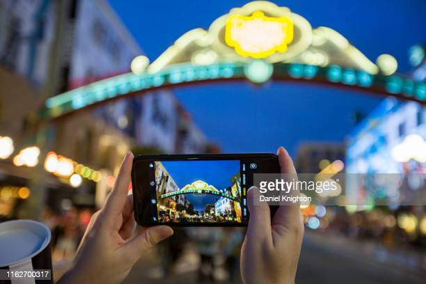 Fan takes a cell phone photo of the iconic San Diego Gaslamp sign on Fifth Avenue outside Comic-Con International Preview Night on July 17, 2019 in...