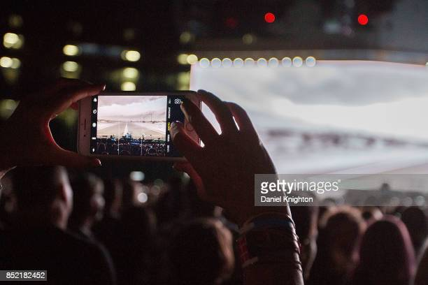 A fan takes a cell phone photo of U2 performing on the final night of U2 The Joshua Tree Tour 2017 at SDCCU Stadium on September 22 2017 in San Diego...