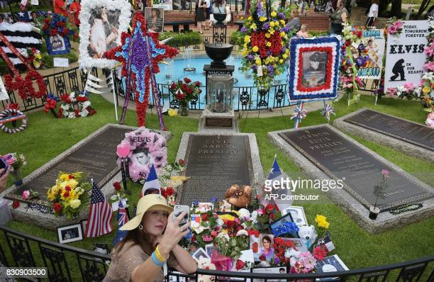 A fan takes a photo of herself at the Meditation Garden where Elvis Presley is buried alongside his parents and grandmother at his Graceland mansion...