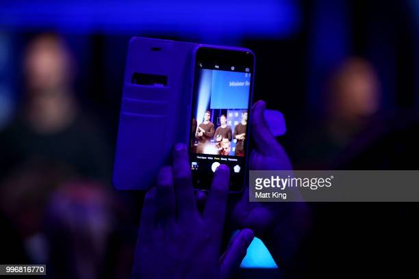 A fan takes a photo of players on stage during a New South Wales Blues public reception after winning the 2018 State of Origin series at The Star on...