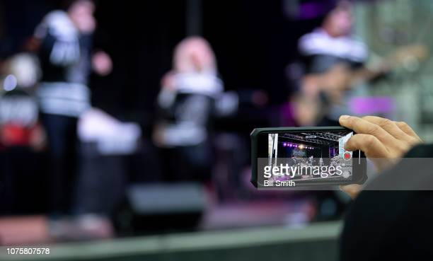 A fan takes a photo of the concert during the Bridgestone NHL Winter Classic Park fan festival at Millenium Park on December 29 2018 in Chicago...