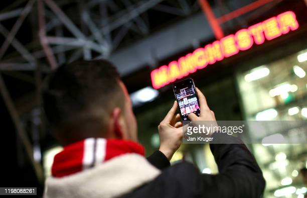 A fan takes a photo on his phone outside the stadium prior to the Carabao Cup Semi Final match between Manchester United and Manchester City at Old...