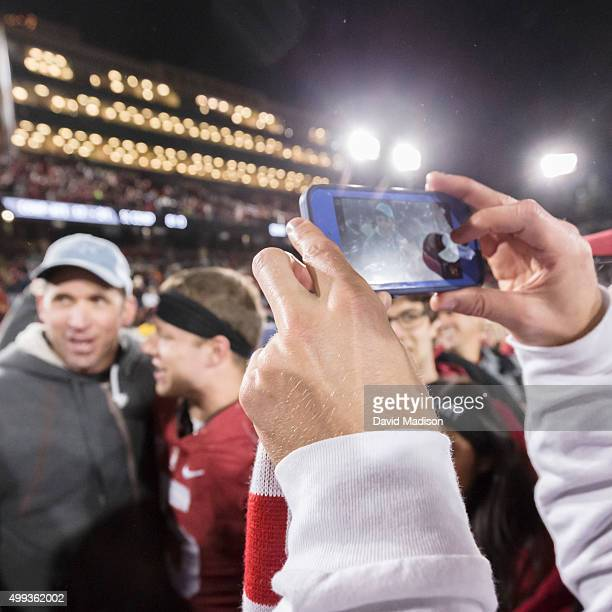 A fan takes a photography of Ed McCaffrey and his son Christian McCaffrey of the Stanford Cardinal following an NCAA football game against the Notre...