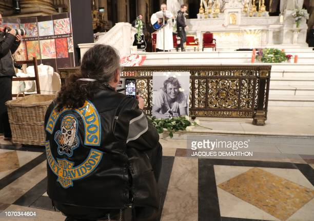 A fan takes a picture during a mass in tribute to French rock singer Johnny Hallyday in Paris on December 9 2018 one year after Johnny's death French...