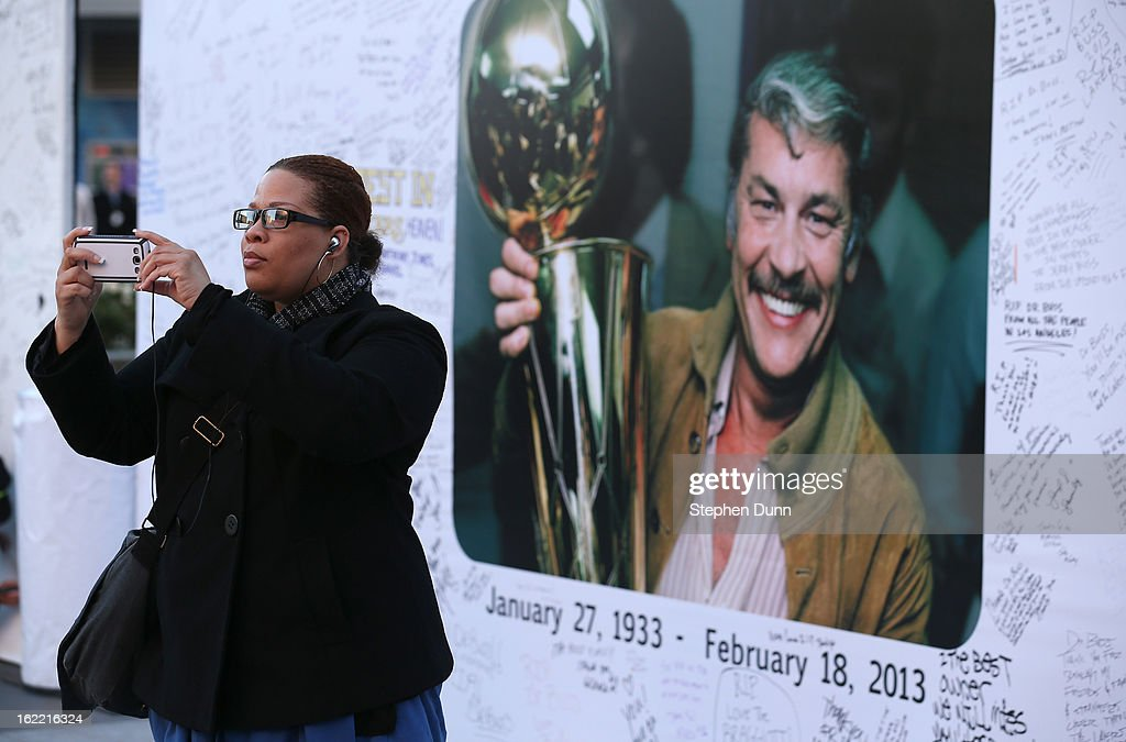 A fan takes a picture of herself in front of a wall near Staples Center in honor of the late Dr. Jerry Buss, owner of the Los Angeles Lakers, before the game against the Boston Celtics on February 20, 2013 in Los Angeles, California.