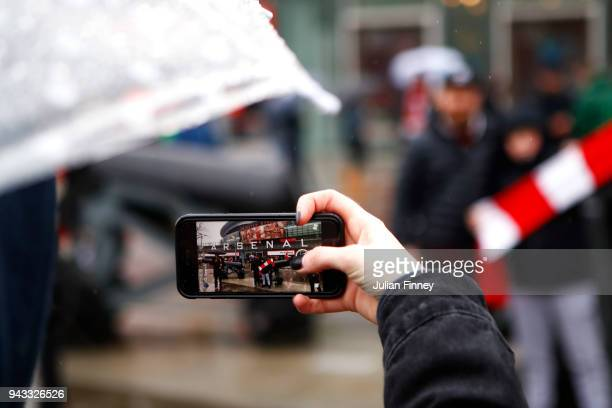 A fan takes a picture of the exterior of the stadium prior to the Premier League match between Arsenal and Southampton at Emirates Stadium on April 8...