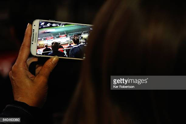 Fan takes a picture on her camera phone during practice for the Le Mans 24 Hour race at the Circuit de la Sarthe on June 15 2016 in Le Mans France