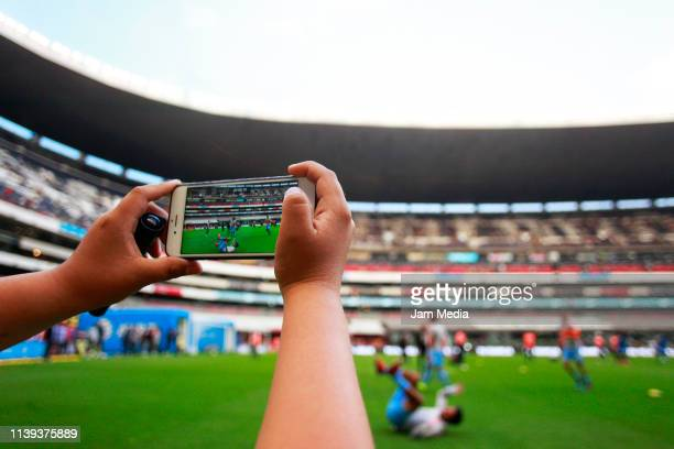 Fan takes a picture with his cellular phone of the Azteca Stadium prior to the 12th round match between America and Tigres UANL as part of the Torneo...