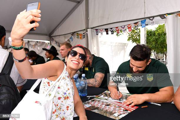 A fan takes a selfie while Josh Mansour of the Kangaroos signs autographs during an Australia Kangaroos and England Lions Signing Session at...