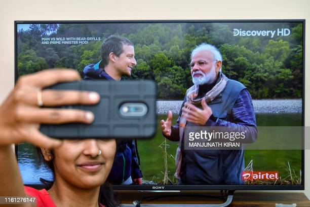 A fan takes a selfie while watching on television the special edition of 'Man Vs Wild' series hosted by survival expert Bear Grylls going on a...