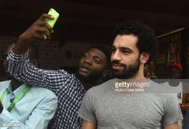 A fan takes a selfie with African Player of the Year Award nominee and Liverpool's Egyptian striker Mohamed Salah before a media briefing on the...