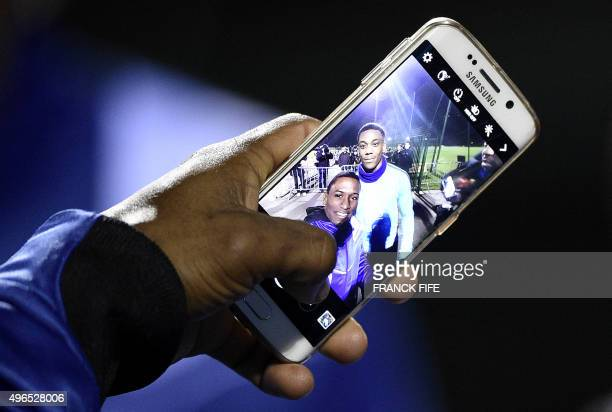A fan takes a selfie with France's forward Anthony Martial during a training session in ClairefontaineenYvelines on November 10 2015 ahead of a...