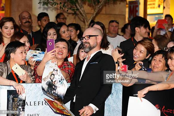 A fan takes a selfie with French film director Cedric NicolasTroyan during The Huntsman Winter's War Premiere at Universal Studios Singapore on April...