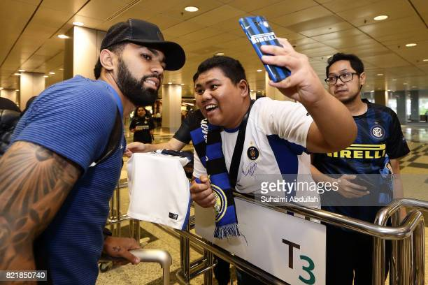 A fan takes a selfie with Gabriel Barbosa of Inter Milan after he arrives at Changi International Airport ahead of the International Champions Cup on...