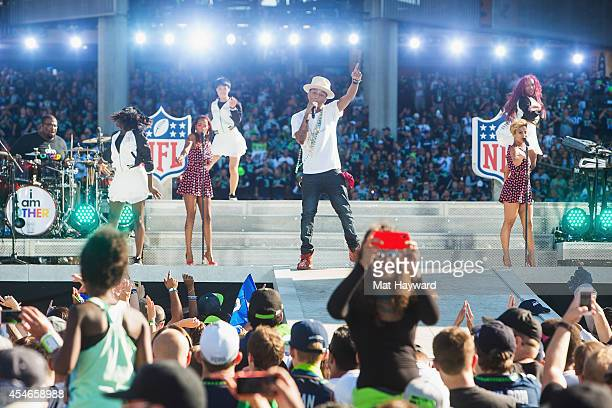 A fan takes a selfie with her back to the stage while Pharrell Williams performs on stage during the NFL Kickoff Concert presented by Xbox before the...
