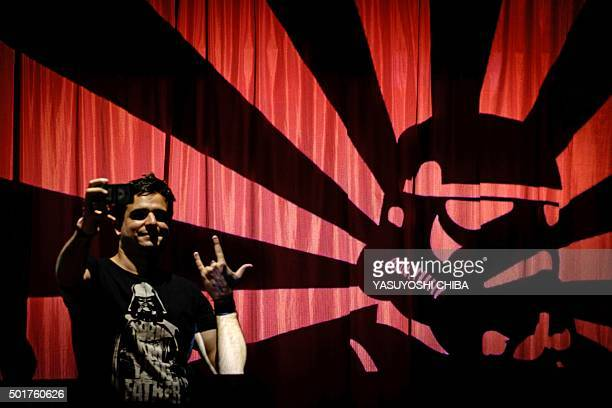 A fan takes a selfie with projected images of the film Star Wars during the opening of the Rio Mapping Festival 2015 on December 17 in Rio de Janeiro...