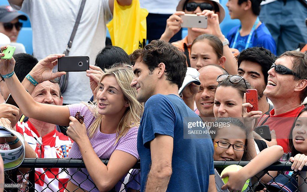 A fan takes a selfie with Roger Federer of Switzerland during a training session at the Brisbane International tennis tournament on January 3, 2016. AFP PHOTO / Saeed KHAN