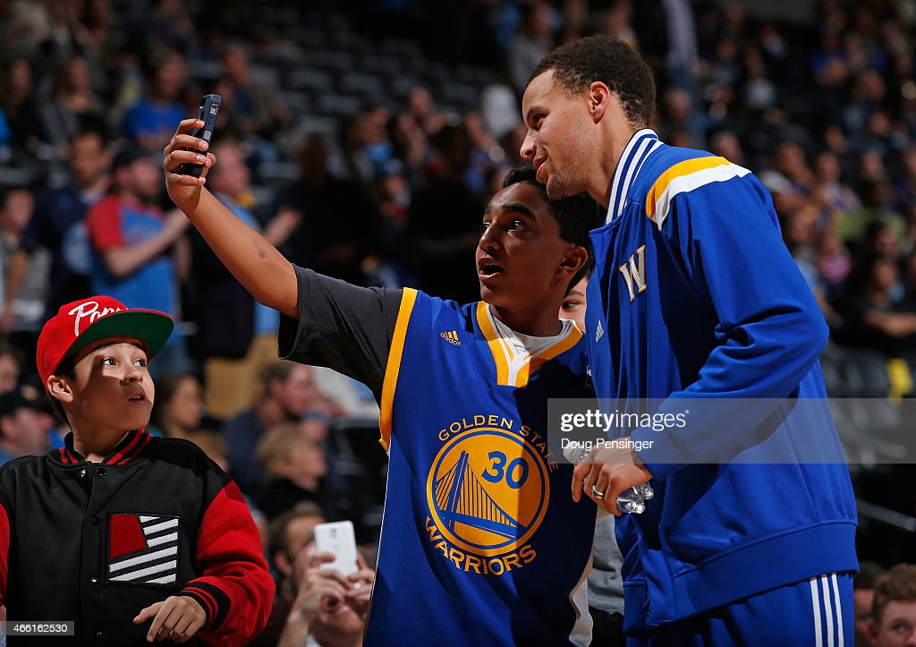 A fan takes a selfie with Stephen Curry #30 of the Golden State Warriors as the Warriors face the Denver Nuggets at Pepsi Center on March 13, 2015 in Denver, Colorado. The Nuggets defeated the Warriors 114-103.