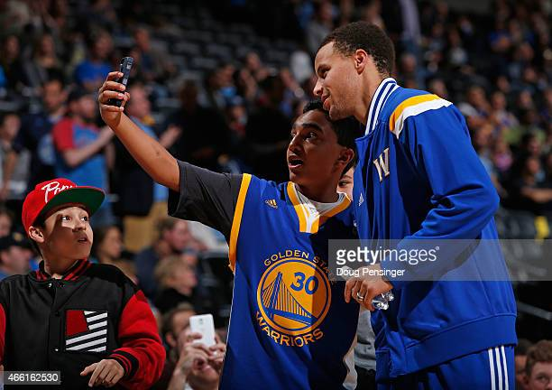 A fan takes a selfie with Stephen Curry of the Golden State Warriors as the Warriors face the Denver Nuggets at Pepsi Center on March 13 2015 in...