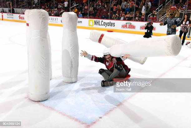 A fan takes part in Human Bowling during the second intermission of a game between the Arizona Coyotes and Edmonton Oilers at Gila River Arena on...