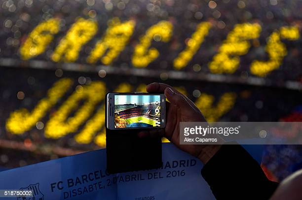 A fan takes photographs as a mosaic in tribute to the former FC Barcelona player and manager Johan Cruyff is unveiled the La Liga match between FC...